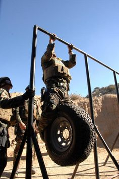 He's in full gear, doing chin-ups, holding a truck tire WITH RIM between his muscular legs.... /dirty thoughts.
