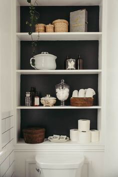 Shelves with a black backdrop highlight supplies above the toilet.