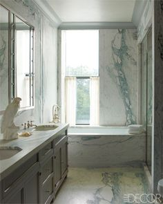 Steven Gambrel ~ Master Bath - Gambrel designed the cabinetry and counter in the master bath; the tub and sink fittings are by Lefroy Brooks, and the floors and walls are Breccia Imperiale marble by Integrated Services.