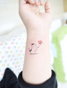 Cat holding a flower tattoo. Small tattoos are perfect for girls and women alike. Delicate and feminine, I promise these 28 blissfully small tattoos will not disappoint. Enjoy!
