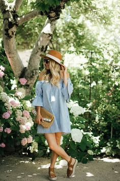 Off the shoulder blue striped dress with bell sleeves, sandals and a straw hat - the perfect summer outfit