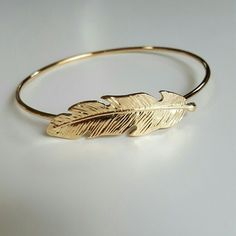 "Golden Feather Bangle This lovely bracelet has a thick Not bendable wire that is 8 1/4"" around and has a feather on the front of it that is 2"" long and 1cm wide. This bangle is brand new and unused, great with your favorite shirt and jeans. Other great bracelets are listed in my closet. Jewelry Bracelets"