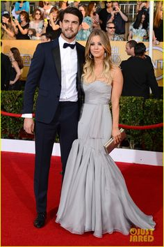 Kaley Cuoco (with hubby Ryan Sweeting) in a dove-grey, strapless mermaid gown by Vera Wang, Ferragamo clutch, Lorraine Schwartz statement earrings and bracelet, and Jimmy Choo 'Raven' platform heels.