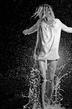 Black and white photography | Young girl splashing in water.