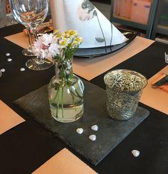 Skifferplade med fyrfadsstage, perler og glasvase med blomster.