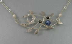 Flying bird sterling silver necklace through tree branches adorned with hand-engraved leaves and flowers and set with a blue kyanite stone  http://www.kryziakreationsstudio.com/products/flying-bird-necklace-with-kyantite $250.00