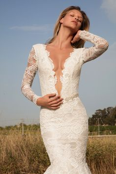 Impressive lace mermaid dress made of antique french lace, adorned by a hand embroidered belt and embroidered appliques. Dress has long sleeves and a very low v- neckline.