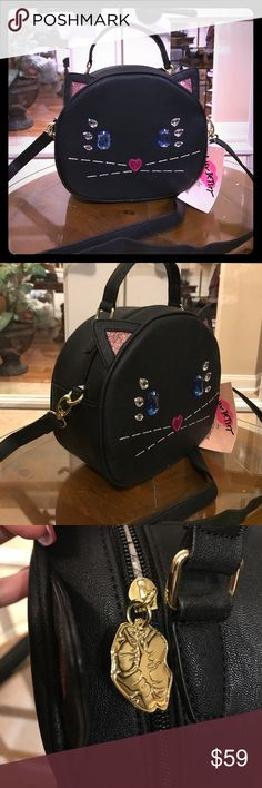 Betsey Johnson Kitty w/ Crossbody Strap This cute little Betsey Johnson Kitty Satchel is so adorable and has an adjustable and removal Crossbody strap if you don't want to carry it.  Main compartment is fully lined and has one zippered pocket and some slip pockets. There is also an exterior pocket on the back of the satchel with a Betsey Johnson name plate attached below.  💋Every gal needs a Betsey!💋 Betsey Johnson Accessories Bags