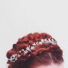 (Jaidelyn's hair for her wedding) Red braids twisted atop her head with an intricate, flowered tiara made of such tiny, delicate stones that you would have thought the blossoms were real had they not caught the light and glimmered with her every breath