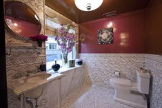 One of the powder rooms is coated in a high-gloss wall finish colored by eyeshadow and layered on in translucent strokes. The tile is a stone-and-mirror mosaic.