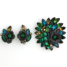 This 1950s Hattie Carnegie brooch and earrings set is an elegant and astonishing combination of layers of blue, green and brown glass stones in black metal.