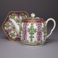 "WORCESTER ?HOP TRELLIS? TEAPOT AND STAND, C.1770-75 of fluted barrel form, painted with alternating panels of green leaves with red berries and purple foliage between lilac and turquoise ground borders embellished with gilding, finial chip, height 5.5"""" ? 14 cm., diameter 5.9"""" ? 15 cm. Provenance: Label with D.M. & P. Manheim, New York Note: A member of the Sèvres style ?Hop Trellis? family, this variant is sometimes known as ?Holly Berry?"