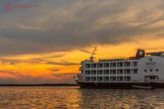navio de cruzeiro da iberostar navega pelo rio solimões durante o pôr do sol com o céu laranja depois de partir de manaus