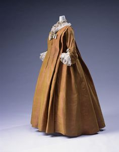"A ""robe volante"", derived from negligee, which was worn during the latter years of the reign of Louis XIV (1638–1715), enjoyed popularity as formal wear in the early 18th century. The large flounce flowed from the shoulders to the ground and was shaped to spread softly over the skirt, characterized this style of gown. Although the corset was worn tightly laced underneath, the loose-fitting robe gave a comfortable and relaxed impression on the outside."