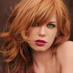 Long wavy copper red hair with subtle copper blonde highlights. Full fringe/bangs
