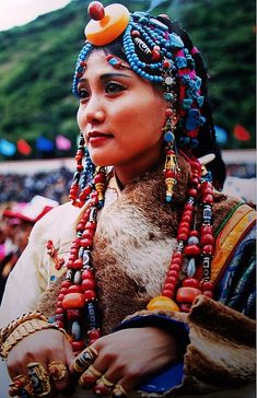 Khampa Tibetan woman wears gold bracelets and traditional tibetan gold rings on every finger at a festival. Both fashion and financial insurance for the family. This kind of ostentation is saved for special occasions