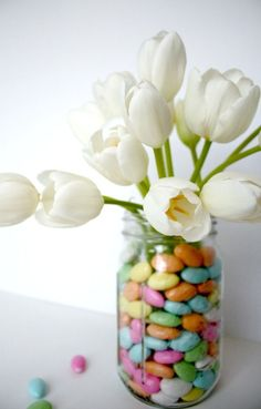 DIY Spring arrangement hack using a water bottle and a large mason jar. Fill with your favorite colored candies and fresh tulips!