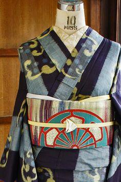 Meisen kimono! Love the funky obi. 市松格子に織り上げられた水浅葱色の縞がアクセントになった黒の地に、雪輪のような波丸文様がリズミカルに織り出された、粋な情緒ただよう銘仙の袷着物です。