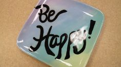 Faded purple, blue, green and yellow glazes together with bold, black text. Be happy! :) Paint Your Own Pottery Design by T. Guidone at Decoy Art Studio in Beavercreek, Oh.