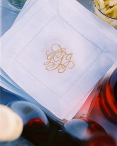 Linen napkins embroidered with flourishing gold monograms