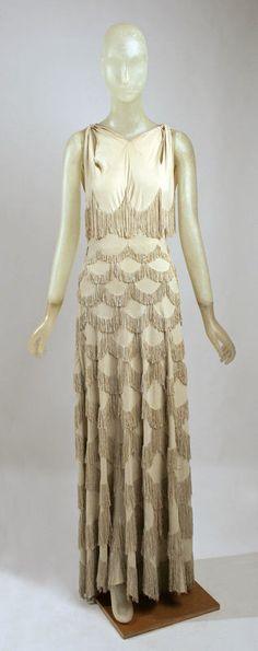 Madeleine Vionnet evening gown. Chất liệu sa tanh và chiffon được sử dụng rất nhiều, và nhờ kĩ thuật cắt chéo vải mà bộ trang phục trở nên ôm sát với cơ thể người phụ nữ.