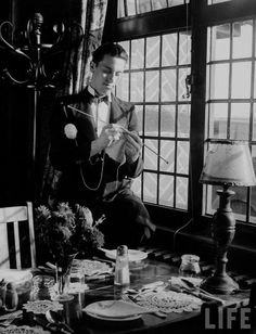 Waiter knitting garments during drive to provide goods to servicemen during the war.