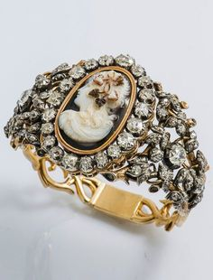 An important antique 18k gold, silver, diamond an agate cameo bracelet, probably French, circa 1850. The 18 carat yellow gold and silver bracelet with a foliate pattern set with old-cut diamonds and centring a three-layered agate cameo representing the profile of Bacchus. The cameo can be detached and be worn as a brooch.