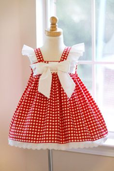 This cute little red gingham dress is charming and beautiful, and can be used for so many occasions. A simple dress and yet stunningly beautiful with a large white bow on the front bodice. The back is