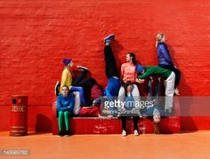 Young people sitting and lying on each other on a red bench.