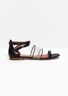 Chic leather sandals accented with a sporty-transparent PU strap, forming a contemporary material contrast.