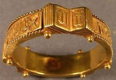 15th Century. Finger-ring, gold, of hollow construction. The hoop is decorated at three points with the motif of an open book. Six, spherical pellets decorate the top and bottom of the hoop at the points where the leaves of the book are placed. Between each book a beaded panel of text is inserted (over a hollow space).  French Inscriptions: cest mon decir (it's my desire). The open books carry two letters each: PO YR EC (for EC)