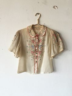1930s cotton gauze peasant blouse with cross stitch embroidery through front bodice, sleeves, and around the peter pan collar. Decorative wooden buttons. Shirring at shoulders
