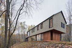 bourgeois / lechasseur wraps canadian house in the woods with cedar shingles