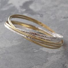 Gold and Silver Russian Bangle - Our Gold and Silver Russian Bangle is an all time classic best-seller this stunning design is actually created with six interlocking bangles - three in sterling silver and three with a golden hued bronze - each with an alternately smooth or hammered finish. #Otisjaxon #Jewellery