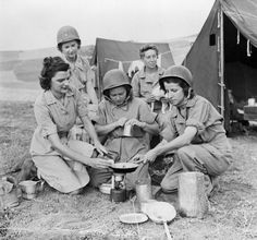 U.S. Army nurses of the staff of an Evacuation Field Hospital behind the lines in Sicily utilize a free moment to prepare a snack over their portable stove; 18 August 1943, Sicily, Italy ~