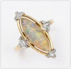 Bague «Marquise» en or jaune ornée d'un cabochon d'opale épaulée de quatre motifs sertis de diamants taillés en rose. (Manque une rose). Vers 1900. | GROS & DELETTREZ