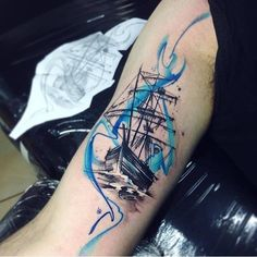 Watercolor full-rigged ship tattoo on the right inner arm.