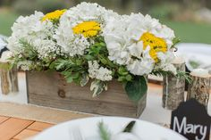 Rustic centerpiece in a barnwood box with white hydrangeas, yarrow, and baby's breath.