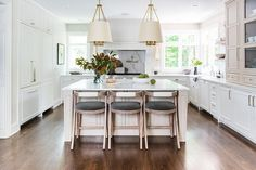 Three curved back wood counter stools sit at a square white and tan island illuminated by two Dalston Hanging Shades. Tan Kitchen, Square Kitchen, Farmhouse Kitchen Island, Gray And White Kitchen, Kitchen Island With Seating, Green Kitchen, Kitchen Time, Kitchen Cabinets, White Counter Stools