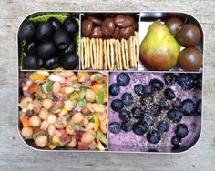 Bean salad, blueberry coconut milk yogurt with blueberries and chia seeds, black olives, crackers, mini pear, black cherry tomatoes, and chocolate covered cherries.