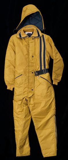 """SAMCO woman's nylon """"Snow-Shield"""" snowmobile suit, circa late 1970s. The suit consists of a one piece hooded jacket and pant suit with leg zippers, a zipper and button front, zippered waist pockets, and a clasp belt."""