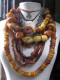 antique natural amber beads from Mauritania and Mali, old pusiostema shell, moroccan and algerian natural coral branches, Idar Oberstein carnelians, an ancient mauritanian shell necklace and an old coral and silver Hamsa moroccan necklace.
