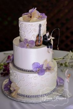 buttercream wedding cake with wafer paper orchids and handmade chocolate guitar #sugarart #weddingcake #waferpaperflowers