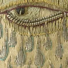 Detail of weeping eye motif showing tears.Magnification 10x. Image by Cristina Balloffet Carr  ca.1600,British. Leather,satin worked with silk and metal thread,seed pearls;satin,couching, and darning stitches;metal bobbin lace;paper. L.12 1/4 x W.6 1/4 inches (31.1 x 15.9 cm) Credit Line:Gift of Mrs. Edward S. Harkness, 1928 (28.220.7, .8)