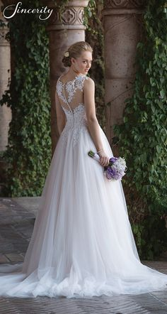 Style 4021: A basque waist ball gown with illusion Sabrina neckline is ready for your Cinderella moment with its Venice lace illusion straps and back. The full tulle skirt is great to dance the night away in on your wedding day.