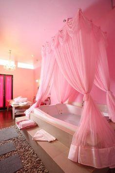 ストロベリーピンクのカーテンに囲まれたバスタブ。ここで半身浴をしたら肌がつやつやになりそうな雰囲気!シャンデリアや扉の濃いめピンクも徹底して甘く女性的。