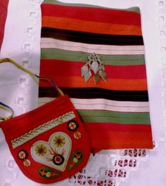 """All items in this auction are from Sweden and quite old. The white """"hardanger"""" linen is NFS. They include: 1-  red, child's purse/bag which  is about 5"""" with a long tie (not original)  and  would have likely been for a toddler. The fabric is from a folkdräkt skirt from Rättvik. It is just a strip of very old wool and probably from a skirt panel. It measures about 21-1/2"""" X 11"""". The heart pendant is also very old and unmarked silver. It measures about 2-1/2""""  long."""