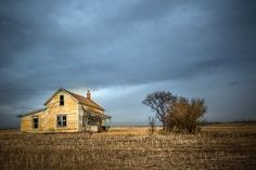 Abandoned yellow farmhouse in a stubble field with blue sky.