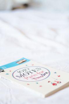 Foto de Melina Souza com o livro Paris for One da Jojo Moyes em cima da cama branca.  Post com fotos dos livros que foram apresentados no Book Haul do mês de Junho.