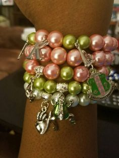 AKA 20 Pearls bracelet set includes Pink and Green 5 stack Bracelets and one bracelet which features 20 pearls and the sororities hand signs. This set is inspired by the ladies of AKA. This set includes a crest charm, an Ivy leaf, the pinkie finger symbol and a silver and green frog and the Greek letters. These can be worn as a set or single.  These bracelets are made with beautiful glass pearl and acrylic beads, on stretch cord for comfort. They come in a standard size 7 but can be…